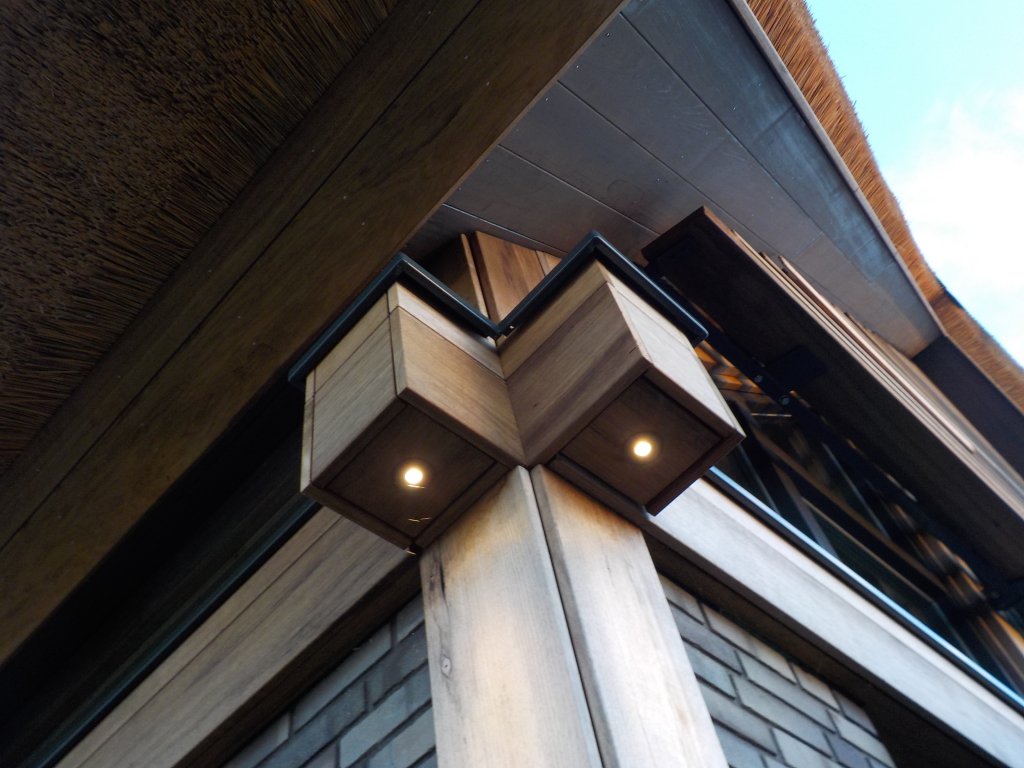Post & beam kolommen en balken van Fraké Noir hout voorzien van LED-verlichting als  accentverlichting. Bijzondere detaillering samenkomt Post & Beam Fraké Noir hout, antraciet pointerwerk metselwerk en de kapconstructie met  onderliggende puien en Fraké Noir lamellen.