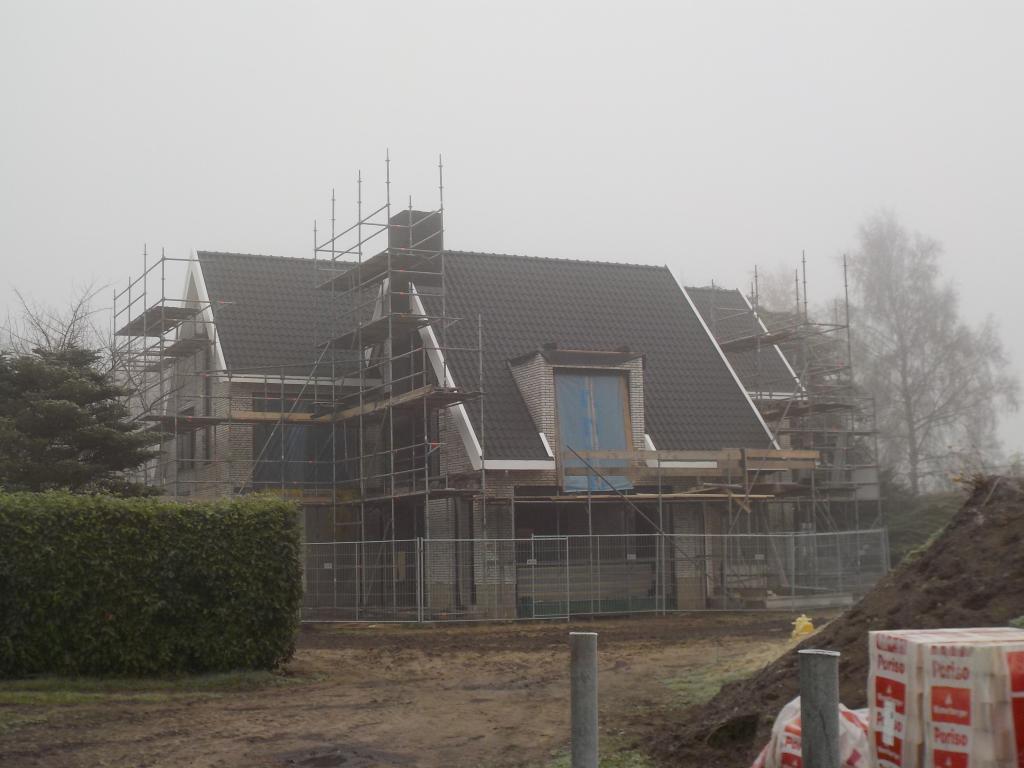 Woning met parallel zadeldak en metselwerk dakkapel.