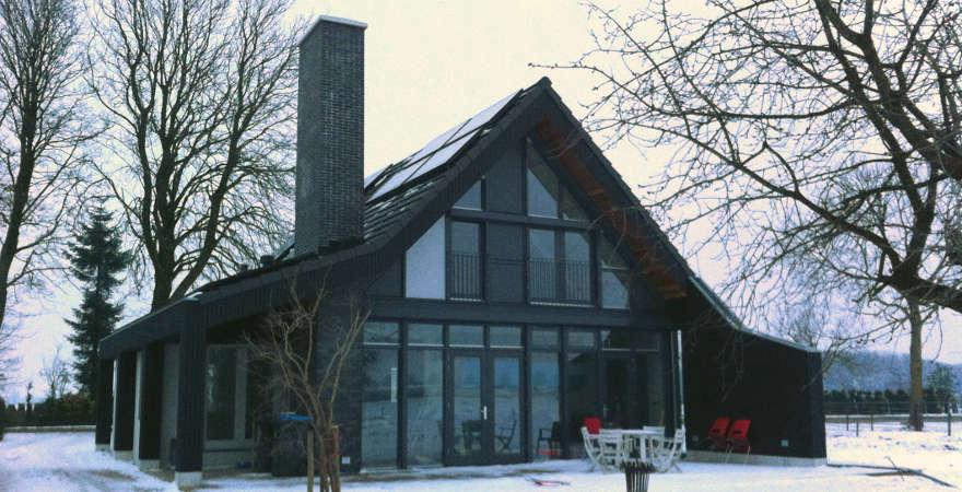 Zwarte strakke woning in wit winterlandschap.