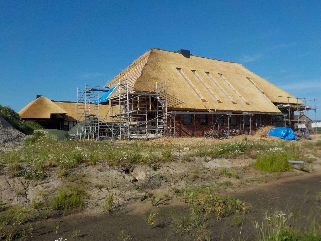 Rietdekker brengt rieten dak aan op woonboerderij Leusden