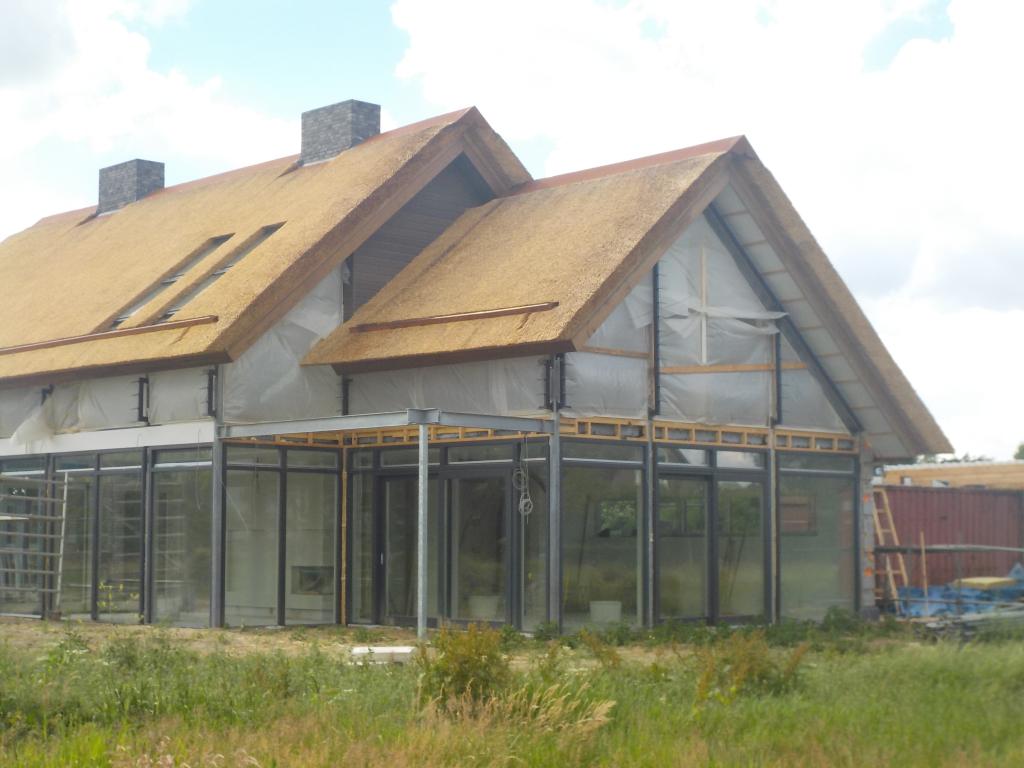Twee rieten daken, een volledig glazen gevel door Post en beam bouwsysteem