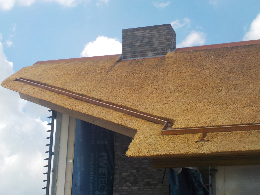 Luxe rietgedekte villa, voorzien van koperen goot in rieten dak en een cortenstalen nok.