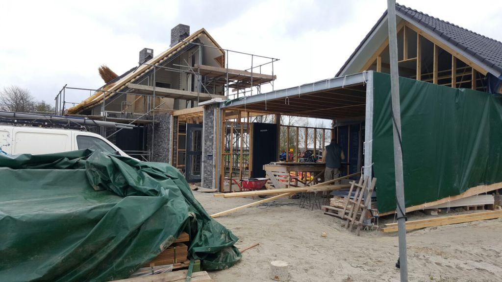 Carport in aanbouw met op de achtergrond de woning en schuur in aanbouw. Draagconstructie nog goed zichtbaar.