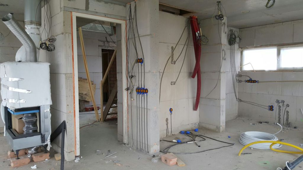 Installaties: plaatsing houthaard, realisatie elektra/water/riool/ventilatie leefkeuken in proces bouw woning.