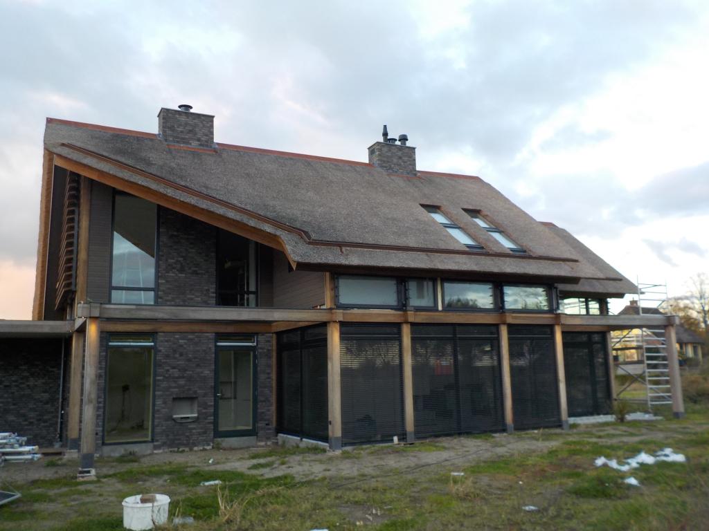 Luxe woning architectuur met natuurlijk materiaalgebruik, chique rieten dak afgedekt met strakke nokvorst van Cortenstaal, Fraké houten Post & Beam structuur voorzien van Luxaflex buitenzonwering.